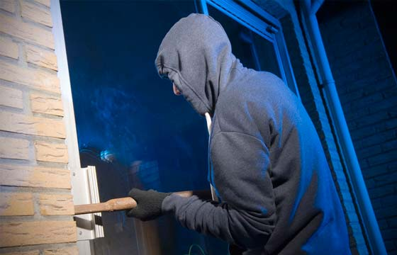 HPG Insurance Works - insurance repairs image of burglar opening a sliding door of a house at night.