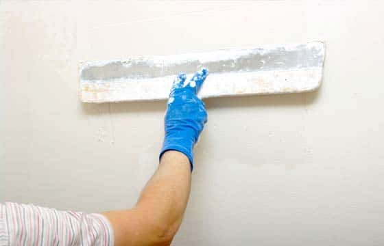 HPG Insurance Works - property maintenance image of a plasterer flushing a wall.