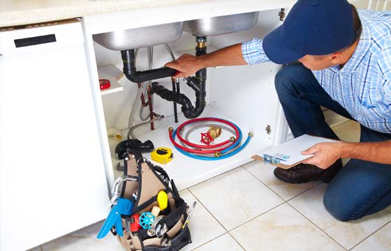 HPG Insurance Works - property maintenance image of a plumber working under a kitchen sink.